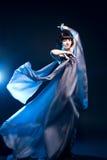 Mädchen in einem grauen Kleidflugwesen mit blauer Hintergrundbeleuchtung Stockfotos