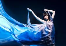 Mädchen in einem grauen Kleidflugwesen mit blauer Hintergrundbeleuchtung Stockbild