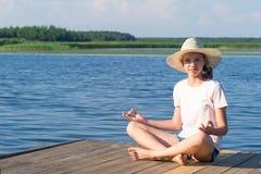 Mädchen in einem großen Hut sitzt in einem Lotussitz von Yoga auf dem Pier an einem sonnigen Tag lizenzfreie stockfotografie
