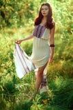 Mädchen in einem hellen Kleid im Wald Stockbild