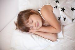 Mädchen in einem hellen Kleid schlafend auf dem Bett Lizenzfreie Stockfotos