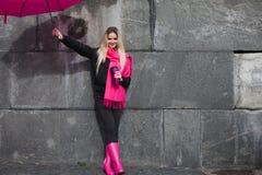 Mädchen in einem hellen rosa Schal, in Gummistiefeln und in einem Regenschirm auf dem Hintergrund der grauen Steinwand Stockbild