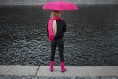 Mädchen in einem hellen rosa Schal, in Gummistiefeln und in einem Regenschirm, die auf den Banken des Flusses, hinter steht Graue Stockfotografie