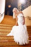 Mädchen in einem Hochzeitskleid, das die Treppen hinuntergeht Lizenzfreies Stockfoto