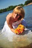 Mädchen in einem Hochzeitskleid im Wasser Stockfotografie
