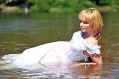 Mädchen in einem Hochzeitskleid im Wasser Stockbild