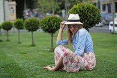 Mädchen in einem Hut auf einem grünen Rasen Stockfotografie