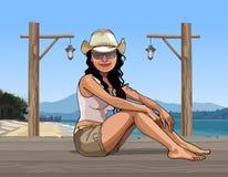 Mädchen in einem Hut, der auf einem Pier im Meer sitzt Stockfotografie