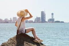 Mädchen in einem Hut, der auf einem Felsen durch das Meer sitzt Stadt im Abstand Sonniger Tag Lizenzfreie Stockfotos