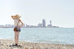 Mädchen in einem Hut, der auf der Küste steht Stadt im Abstand Ansicht von der Rückseite Stockfoto