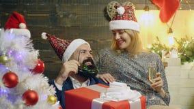 Mädchen in einem Hut des neuen Jahres, der nahe dem bärtigen Mann hält einen großen roten Kasten mit Geschenken auf dem Hintergru stock video