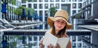 Mädchen in einem Hut ein Buch durch das Pool lesend stockfoto