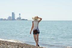 Mädchen in einem Hut geht entlang die Küste Stadt im Abstand Ansicht von der Rückseite Lizenzfreie Stockbilder