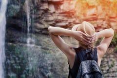 Mädchen in einem Hut mit dem Rucksack, der einen Wasserfall betrachtet Hände hinter dem Kopf Ansicht von der Rückseite stockbild
