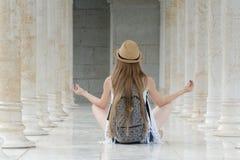 Mädchen in einem Hut mit einem Rucksack, der im Lotussitz unter den Marmorsäulen sitzt Rückseitige Ansicht Lizenzfreies Stockbild