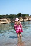 Mädchen in einem Hut und in einem Kleid, die in einem seichten Meerwasser stehen Lizenzfreies Stockfoto
