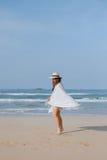 Mädchen in einem Hut und in einem Plaid geht entlang den Strand Lizenzfreie Stockbilder