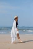 Mädchen in einem Hut und in einem Plaid geht entlang den Strand Lizenzfreie Stockfotos