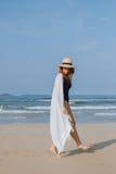 Mädchen in einem Hut und in einem Plaid geht entlang den Strand Lizenzfreies Stockbild