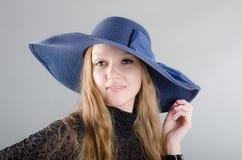 Mädchen in einem Hut und in einem schwarzen Kleid Stockfotografie