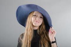 Mädchen in einem Hut und in einem schwarzen Kleid Stockfotos
