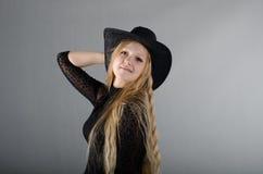 Mädchen in einem Hut und in einem schwarzen Kleid Lizenzfreies Stockfoto