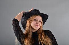 Mädchen in einem Hut und in einem schwarzen Kleid Lizenzfreie Stockfotos