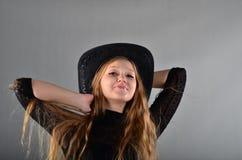 Mädchen in einem Hut und in einem schwarzen Kleid Stockfoto