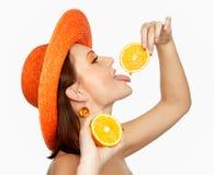 Mädchen in einem Hut und mit Orangen Stockbilder