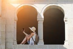 Mädchen in einem Hut und mit einem Rucksack, der im Bogen eines alten Fensters sitzt, macht selfie Von unterhalb Verkürzung zeich Lizenzfreie Stockfotos