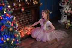 Mädchen in einem intelligenten rosa Kleid im Weihnachten Stockfoto