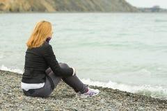 Mädchen an einem kühlen Tag, der auf Strand sitzt und durchdacht den Abstand untersucht Stockbilder