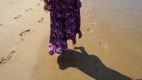 Mädchen in einem Kleid, barfuß laufend auf dem Strand Goldener Sand hinterlässt Spuren, Rolle der Wellen allmählich stock video footage