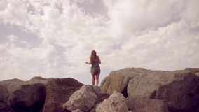 Mädchen in einem Kleid, das auf einen Berg steht und die Abstand Zeitlupe untersucht stock video