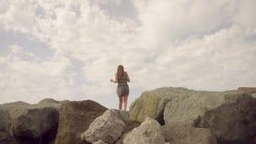 Mädchen in einem Kleid, das auf einen Berg steht und die Abstand Zeitlupe untersucht stock footage