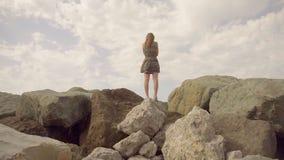 Mädchen in einem Kleid, das auf einen Berg steht und die Abstand Zeitlupe untersucht stock video footage