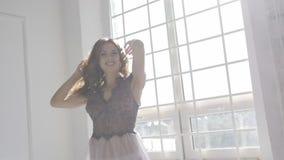 Mädchen in einem Kleid gegen das Fenster stock footage