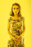 Mädchen in einem Kleid mit einem Blumendruck im gelben Licht Lizenzfreie Stockfotos