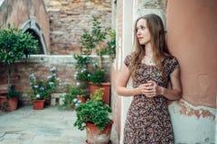 Mädchen in einem Kleid schlendert durch einen gemütlichen alten Hof Stockfotos