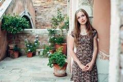 Mädchen in einem Kleid schlendert durch einen gemütlichen alten Hof Stockbild