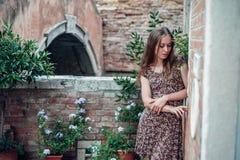 Mädchen in einem Kleid schlendert durch einen gemütlichen alten Hof Lizenzfreie Stockfotos