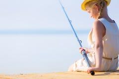 Mädchen in einem Kleid und in einem Hut mit einer Angelrute Stockfotografie