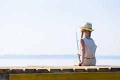 Mädchen in einem Kleid und in einem Hut mit einer Angelrute Stockfoto