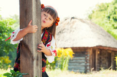 Mädchen in einem Kranz und eine Klage mit der ukrainischen Verzierung in der Landschaft mit Holzhäusern Lizenzfreies Stockbild