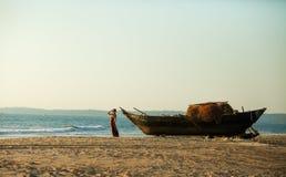 Mädchen in einem langen Kleid, das am alten Boot auf dem Strand aufwirft Stockfotografie