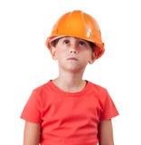 Mädchen in einem orange Sturzhelm, der oben schaut Stockfotos