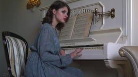 Mädchen in einem peignoir, das nahe einem Klavier sitzt stock footage