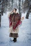 Mädchen in einem Pelzmantel auf einem Weg im Park und im Genießen eines Wintertages stockfotos