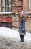 Mädchen in einem rosa Barett und in einem grau-blauen Mantel, die im Yard des alten Hauses stehen Lizenzfreie Stockfotografie