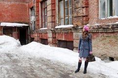 Mädchen in einem rosa Barett und in einem grau-blauen Mantel, die im Yard des alten Hauses stehen Stockfotos